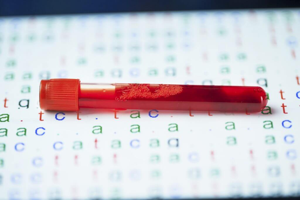 blood sample in test tube with DNA code behind